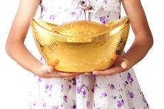 Holding gold ingot. Girl holding a chinese gold ingot in her hand royalty free stock photos