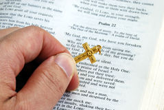 Holding a golden cross while reading the bible Stock Photos