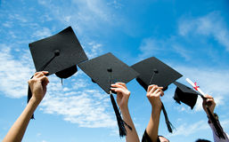 Holding graduation hats. Many hand holding graduation hats on background of blue sky Royalty Free Stock Photo