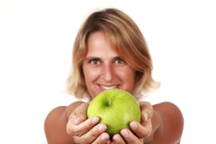 Holding a green apple. Portrait of a young beautiful woman holding a green apple Royalty Free Stock Photos