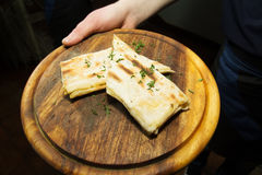 Holding in hand armenian lavash bread. Thin armenian lavash bread. pita bread on a wooden tray Stock Images