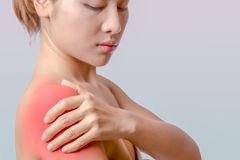 Holding hand on right shoulder. Asian woman holding left hand on right shoulder, young woman pain at right deltoid muscle stock photos