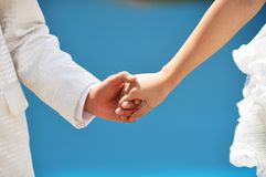 Holding Hands. Bride and groom's hand are holding together Royalty Free Stock Images