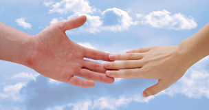 Holding hands. Clouds royalty free stock photo