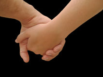 Holding hands. Close up of young couple holding hands, isolated on black Stock Image