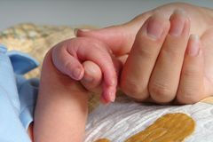Holding Hands. A newborn baby holding on to his mom's hand stock photos