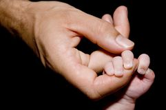 Holding Hands. A young baby holds on to daddy's finger Royalty Free Stock Photography