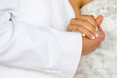 Holding hands. A horizontal photo of a caucasian bride and groom holding hands during a wedding reception Royalty Free Stock Images