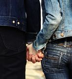 Holding hands. Pair of young people dressed casually walking holding hands Royalty Free Stock Photography