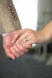 Holding Hands. A young Caucasian couple holding hands with and engagement ring visible Stock Photos