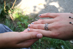Holding hands. Two hands one with manicure and painted fingernails stock photo