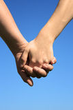 Holding by hands. Couple holding by hands on a sky Royalty Free Stock Photos