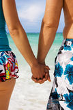 Holding hands. A young couple holding hands on the beach in Cuba Stock Photo
