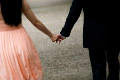 Holding Hands. Man and woman holding hands and walking stock image