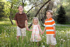 Holding Hands. Three young blond siblings in summer attire holding hands and smiling in nature Stock Photos