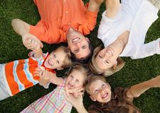 Holding Hands. Young Caucasian family lying on the grass together holding hands and smiling Stock Photos