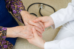 Holding the hands. The doctor holding an elderly woman's hand Royalty Free Stock Image