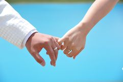 Holding hands in blue background. Bride and groom's hand are holding together Royalty Free Stock Photos