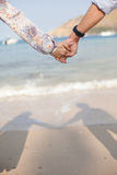Holding hands couple on beach with shadow. Royalty Free Stock Photos