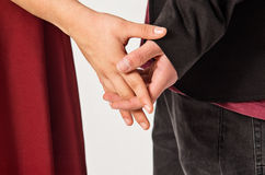 Holding Hands. Detail of a loving couple holding hands with interlaced fingers stock images