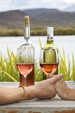 Holding hands &drinking wine. Two hands with a wine glasses and bottles on a scenic background Stock Photography