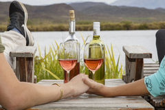 Holding hands & drinking wine. Two hands with a wine glasses and bottles on a scenic background Stock Image