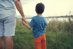 Holding hands father. Father and son holding hands looking out over the lake at the mountain at sunset Royalty Free Stock Photography
