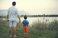 Holding hands father. Father and son holding hands looking out over the lake at the mountain at sunset Royalty Free Stock Photos