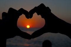 Holding hands in heart shape. With sun immersing at the horizon Stock Image