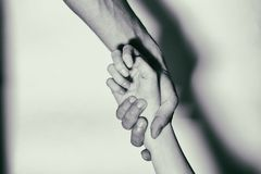 Help to drug addicts. Hand-aid addicts. Black and White. Holding hands for helping drug addict teenage on white background. Stop drug addiction by rehabilitation stock photo