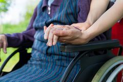 Holding hands - Parkinson disease. Close up picture of carer holding elderly woman`s shaking hands, sitting in a wheelchair - Parkinson disease Stock Photography