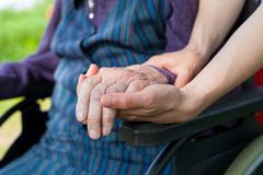 Holding hands - Parkinson disease. Close up picture of carer holding elderly woman`s shaking hands, sitting in a wheelchair - Parkinson disease Royalty Free Stock Image