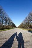 Holding hands shadow down a long path Royalty Free Stock Image