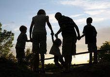 Holding Hands Silhouette. Silhouette of young family outdoors holding hands Royalty Free Stock Image