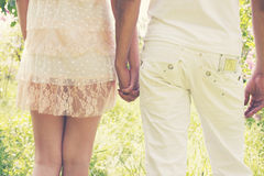 Holding hands, tinted. Young couple walking in the park holding hands Stock Photography