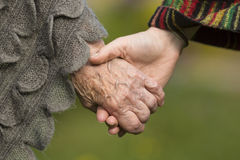 Holding hands together - old and young. Love. Holding hands together - old and young, close-up outdoors Royalty Free Stock Images