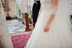 Holding hands of wedding couple at church ceremony. Royalty Free Stock Photography