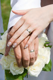 Holding hands with wedding rings Stock Photo