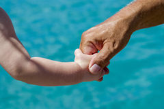 Holding hands. Young and old holding hands with tropical waters as backdrop Stock Image