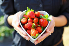 Strawberry in heart shape bowl with hand Stock Image