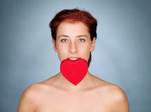 Holding heart with her teeth Royalty Free Stock Images