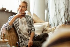Beaming blonde woman in black pants resting on a sofa. Holding heavy teapot. Beaming blonde woman in black pants resting on a sofa and getting fresh tea from a stock photography