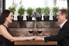 Holding her hand. Happy mature couple sitting at the restaurant Stock Photo