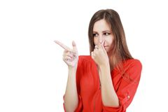 Holding her nose. Portrait of a young woman holding her nose because of a bad smell royalty free stock photos