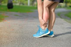 Holding his sports leg injury, muscle painful during training. Young fitness woman holding his sports leg injury, muscle painful during training. Asian runner stock photography