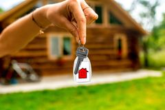 Holding house key with wooden cottage on Stock Image