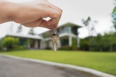 Holding house keys on house shaped in front of a new home stock photo