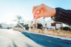 Holding house keys on house shaped keychain closeup in front of a new home. Holding house keys on house shaped keychain in front of a new home Royalty Free Stock Photo