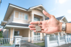 Holding house keys on house shaped keychain in front of a new ho Stock Image