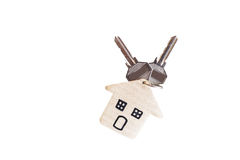 Holding house keys on house shaped keychain in front of a new ho Royalty Free Stock Images
